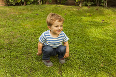 Full shot portrait cute smiley baby boy squat in the grass stock images