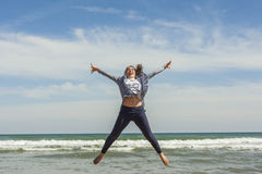Full shot of a smily teenager jumping in the seashore of the bea Royalty Free Stock Photography
