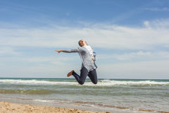 Full shot of a smily teenager jumping in the seashore of the bea Royalty Free Stock Images
