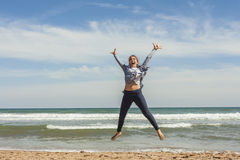 Full shot of a smily teenager jumping in the seashore of the bea Stock Photos