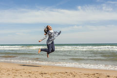 Full shot of a smily teenager jumping in the seashore of the bea Royalty Free Stock Photo