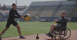 Wheelchaired athlete and trainer throwing medicine ball. Full shot of a wheelchaired athlete and his trainer working out with a medicine ball stock footage