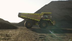 A yellow truck on a quarry. A full shot of a yellow truck moving forward. Camera tracks the truck`s movements stock footage