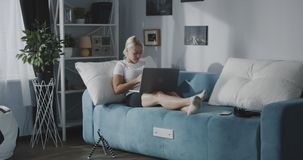 Woman using laptop at home. Full shot of a young woman using a laptop while sitting on a sofa at home stock footage