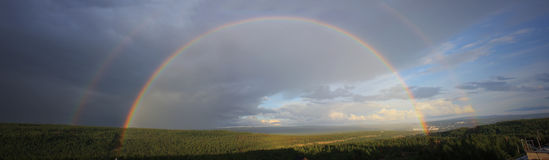 Full size double rainbow. Above the forest Stock Photography