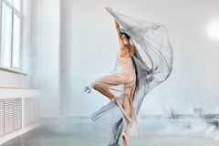 Female ballet dancer with white flowing fabric. Flow shapes and movement. royalty free stock photography