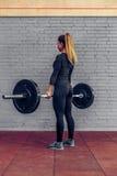 Full skivstång för ung kvinna för längd lyftande i idrottshall royaltyfri fotografi