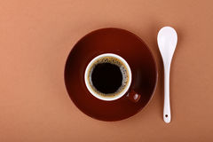 Full small brown cup of black coffee on parchment Stock Photo