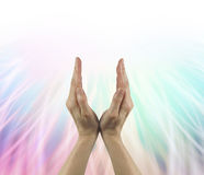 Full Spectrum White Light Healing Energy. Female hands reaching up into white light with a background of rainbow colored linear light royalty free stock images