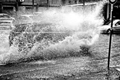 At full speed. Civitavecchia Italy bad weather a car crosses a large puddle at full speed creating a wave of water on the road. The heavy rains have created stock images