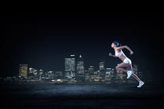 At full speed. Young woman athlete running fast on dark background Stock Images