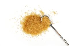 Full spoon and pinch of brown cane sugar on white Stock Images