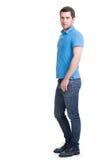Full stående av att le den lyckliga stiliga mannen i blå t-skjorta royaltyfria bilder