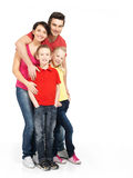 Full stående av den lyckliga unga familjen med två barn Royaltyfri Bild