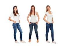 Full stående av tre tillfälliga flickor med jeans och vittshirts Royaltyfria Bilder