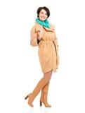 Full stående av den lyckliga kvinnan i beige höstlag med gröna avskummar Arkivfoton