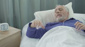 Full of strength and energy man waking up in his cozy bed rejoicing to new day. Stock footage stock footage