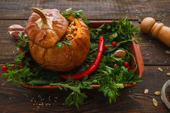 Full stuffed pumpkin on tray with green top view. Prepared squash with fresh vegetables on kitchen table. Seasonal menu, vegetarian cuisine, healthy food Stock Photography