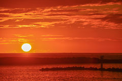 Full sun sunset over water. Full sun setting over water with cloudy orange sky Stock Photography