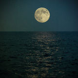 Full super moon under the see. Gietting the light on water Royalty Free Stock Images