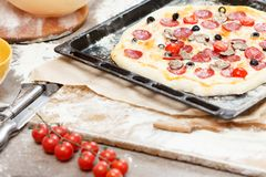 Full supreme pizza baked fresh out of the oven next to ingredients. Delicious cheese full supreme pizza baked fresh out of the oven next to ingredients royalty free stock photo