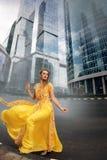 Full tillväxtstående av den trendiga kvinnan på stads- bakgrund Arkivfoto