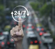Full time service concept. Hand pressing button 24 hours service icon over blur of rush hour with cars and road, Full time service concept Royalty Free Stock Photos