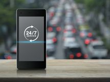 Full time service concept. 24 hours service icon on modern smart phone screen on wooden table over blur of rush hour with cars and road, Full time service Stock Photo