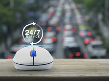 Full time service concept. 24 hours service icon with wireless computer mouse on wooden table over blur of rush hour with cars and road, Full time service Royalty Free Stock Photos