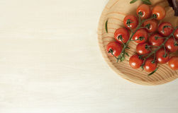 Full top view of pile of cherry tomatoes in the wooden board. On white board for background Stock Photo