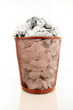 Full Trash Bin. Trash bin is filled with paper waste isolated on white background Stock Photo