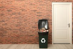 Full trash bin near brick wall indoors, space for text. Waste recycling royalty free stock image