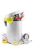 Full trash can. Over full trash can with garbage lying around it on white Royalty Free Stock Image