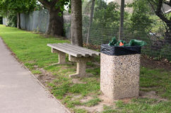 Full trash can next to empty bench. A full rubbish bin makes an empty bench an unwelcoming place to rest Royalty Free Stock Photos