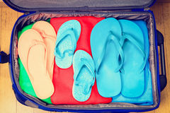 Full travel suitcase with clothing and flip-flops Royalty Free Stock Photos
