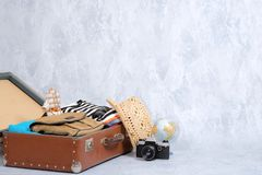 Full travel suitcase on grey background, opened case with travel clothing, accessories. Banner mockup with copy space. Travel or t. Ourism, vacation, holiday royalty free stock photography