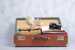 Full travel suitcase on grey background, opened case with travel clothing and accessories. Travel or tourism, vacation, holiday concept stock photo