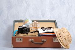 Full travel suitcase on grey background, opened case with travel clothing and accessories. Travel or tourism, vacation, holiday concept royalty free stock photography