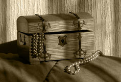 Full of treasures. Wooden treasure chest filled with jewellery royalty free stock photography