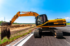 Full utility Excavator working on side of road construction site Stock Photos