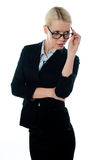 Full view of attractive businesswoman looking away. From beneath her glasses Royalty Free Stock Images