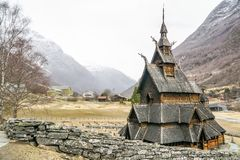 Full view of intricate stave church in Norway surrounded by rock wall royalty free stock images