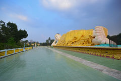 Full view of large Mya Tha Lyaung Reclining Buddha with the large space in front with floor tiles royalty free stock photography