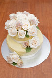 Full view of wedding cake. Wedding cake with cream and latte roses and a white chocolate ganache sitting on a wooden table Stock Image