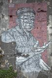 Full view of work of art, painting on exterior wall of building, with illustration of older man, very expressive stock photo