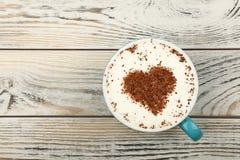 Full vit kopp av cappuccinokaffe på wood plankor fotografering för bildbyråer