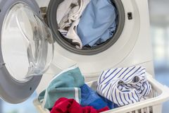 Full Washing machine and clothes in basket on white background Stock Photography