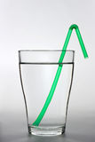A full water glass with a green drinking straw Stock Images