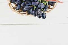 Full wicker basket of fresh ripe blue grapes on old wooden white planks. Full wicker basket of fresh ripe blue grapes on old wooden rustic white planks royalty free stock image