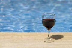 Full wine glass near the pools edge. Stock Photography